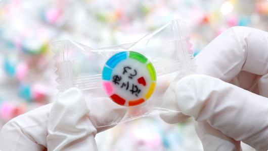 個包装された飴を目視で一つ一つ手作業で引っくり返します。